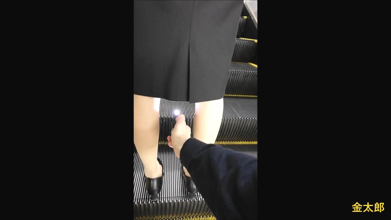 前の女性の脚の間にデジカメを差し込む