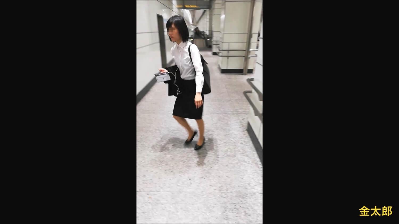 撮影者が前から来たので歩く方向を変えるリクルートスーツの女性