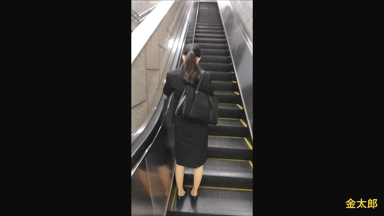 エスカレーターを昇るリクルートスーツを着た女性