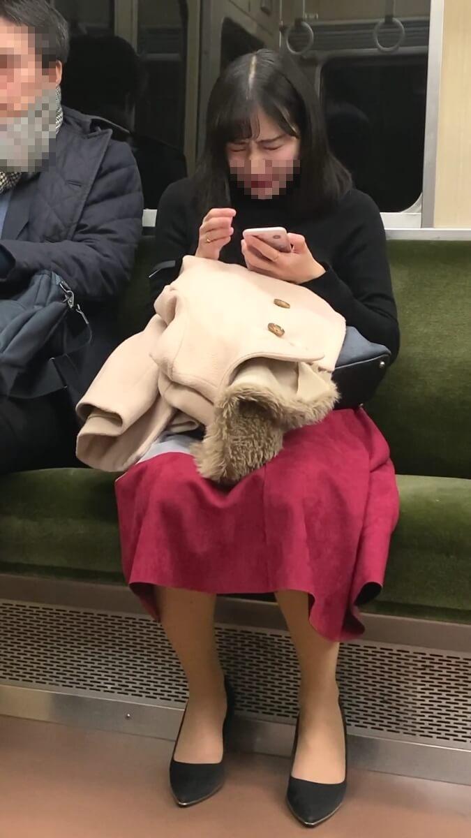 電車内でくしゃみをする美人女性