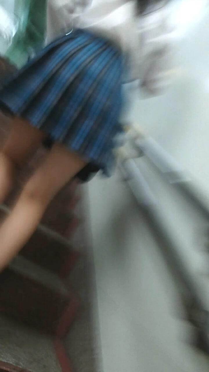 階段を上がる青チェックスカートのJK