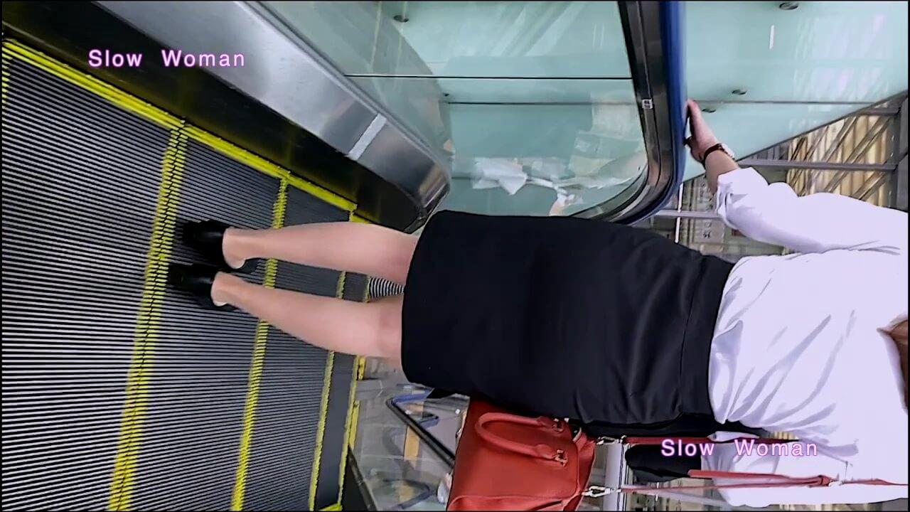 エスカレーターに乗るリクルートスーツの女性