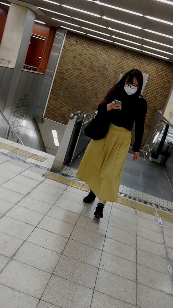 駅構内を歩くロングスカートの女性