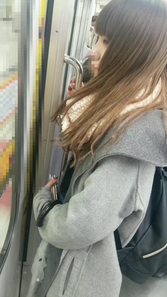 電車の窓際に立つ綺麗な女性