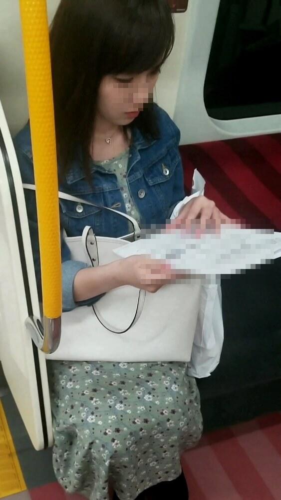 可愛い女性が電車の座席に座ってる