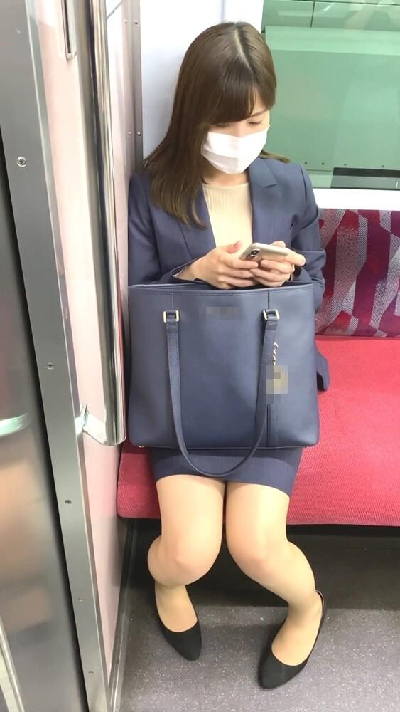 電車の座席に座るスーツ姿のOL
