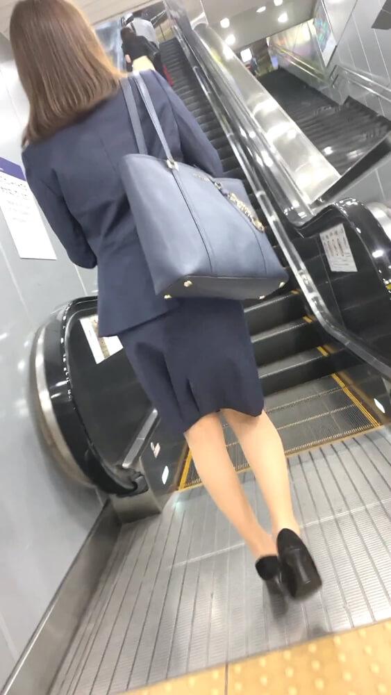 エスカレーターに乗る前のスーツ姿のOL