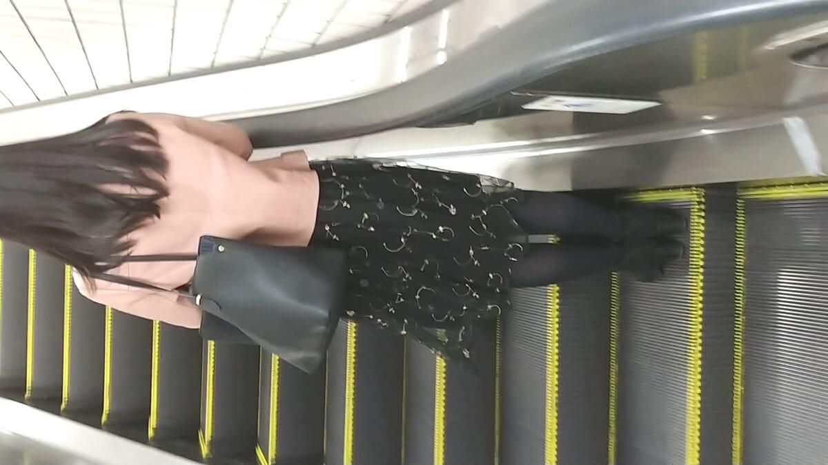 脚のきれいな黒タイツを履いた女性の後ろ姿