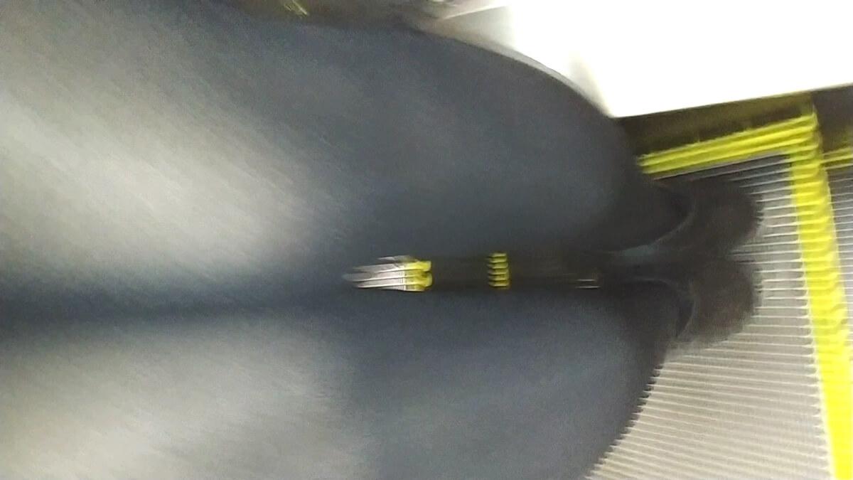 黒タイツを履いた女性のスカートの中にスマホを差し入れる