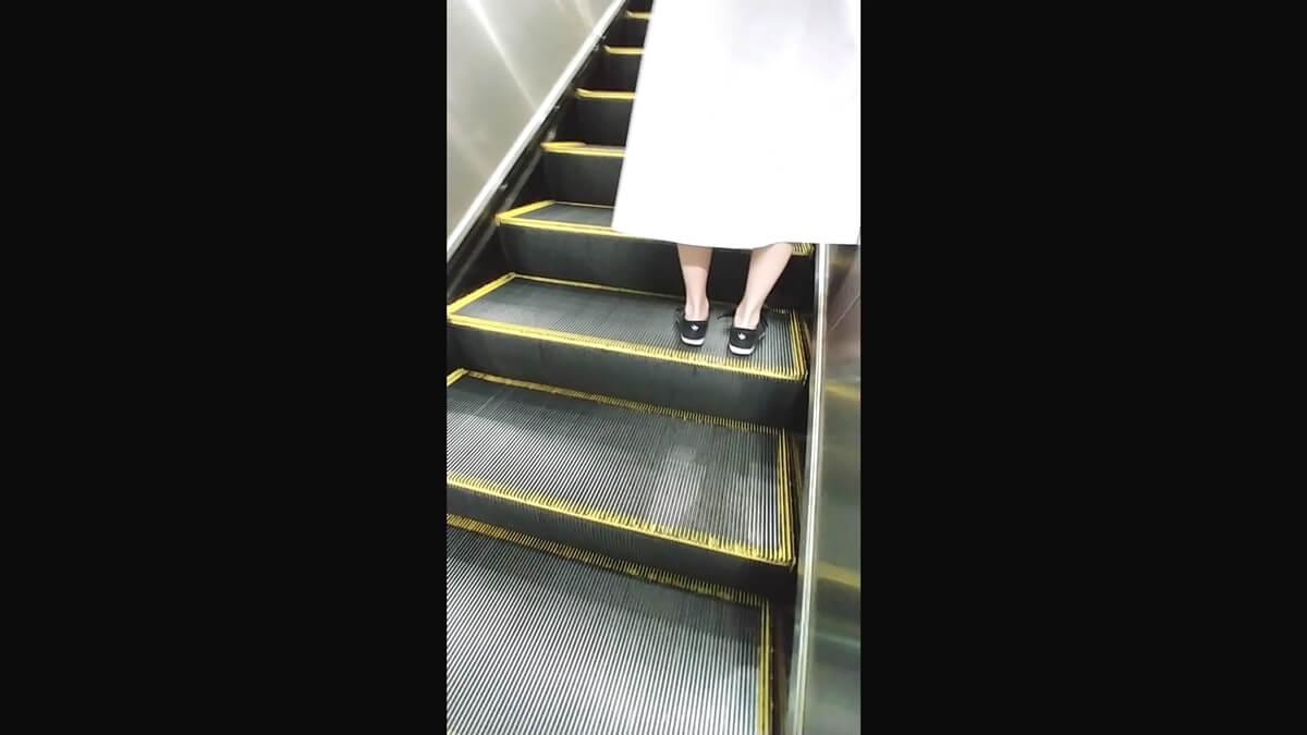 エスカレーターに乗るロングスカートの女性