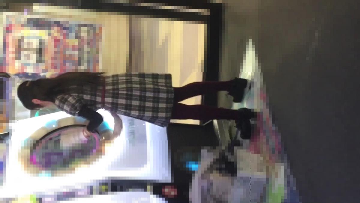 本気モードでゲーセンのゲームをしてる紫色タイツを履いた女性