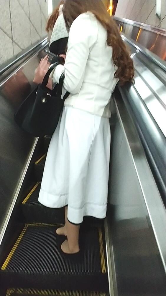 後ろを意識してエスカレーター上で斜めに立つ女性