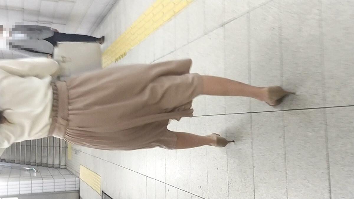 駅のホームを颯爽と歩く女性