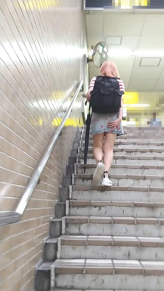 ミニスカートを押さえながら階段を上がる女性