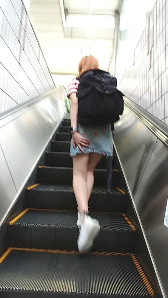 スカートを押さえながらエスカレーターを昇っていく女性