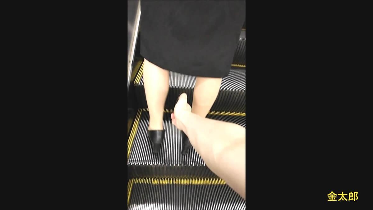 エスカレーターの上でバランスを崩すリクスー女性