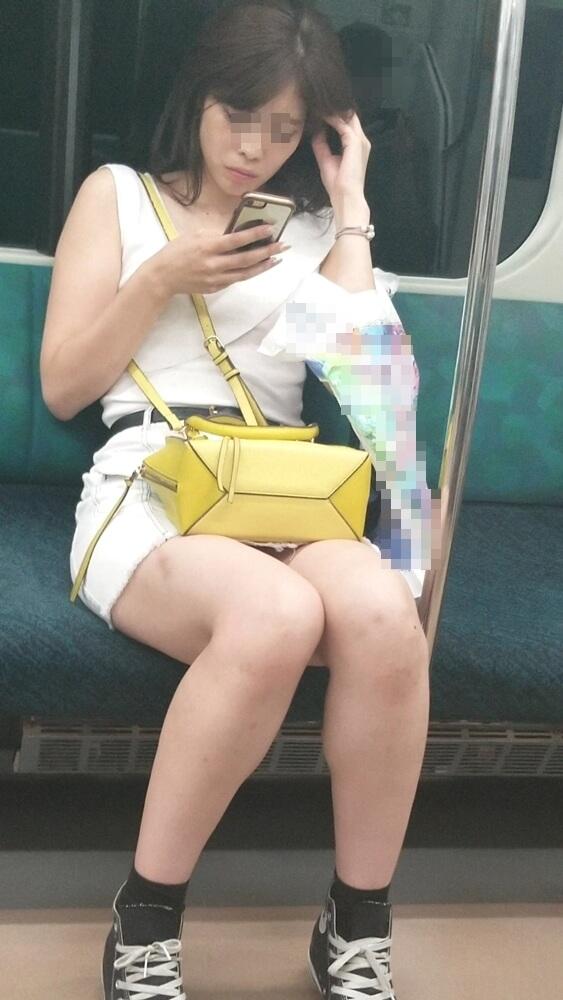 電車の座席に座るミニスカ女性