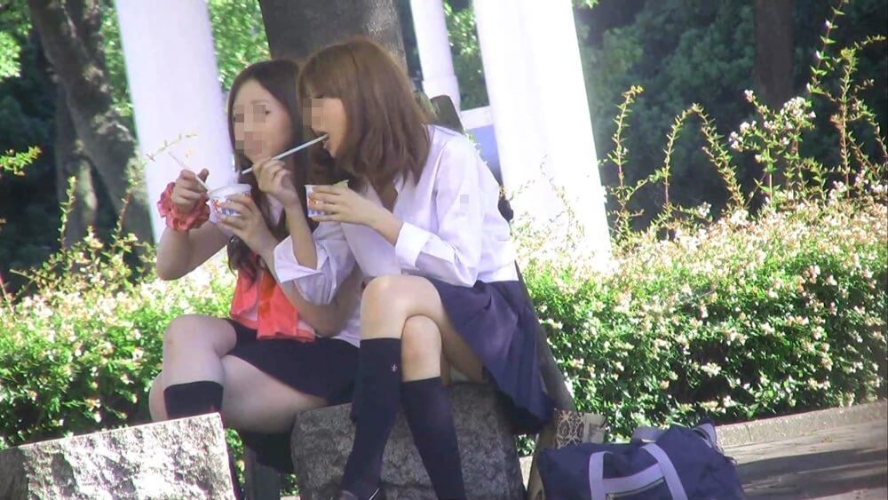 公園で座ってかき氷を食べる制服JK
