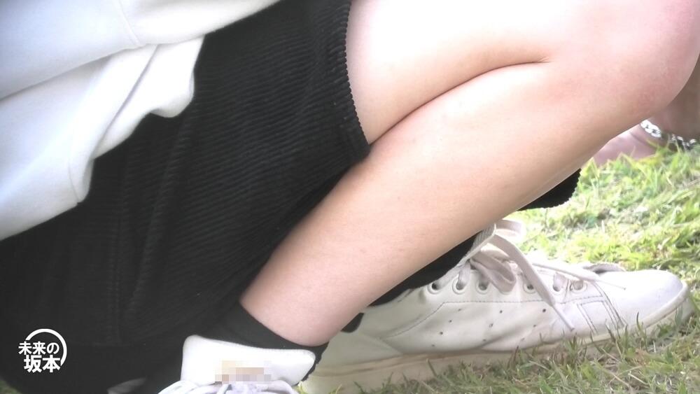 芝生の上にしゃがむ女子