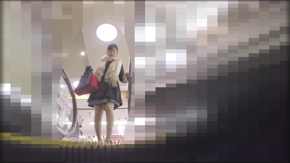 エスカレーターに乗る女性の画像