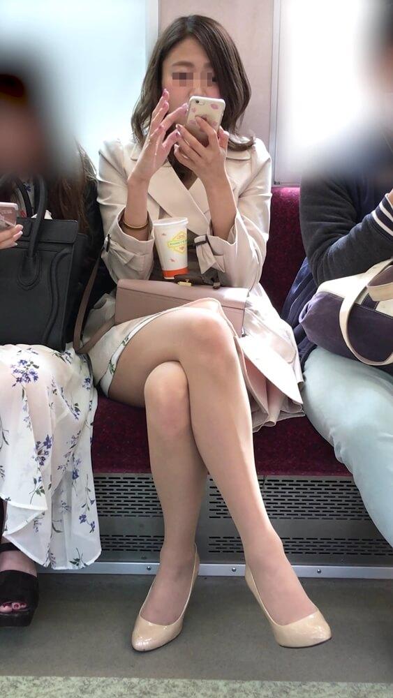 電車内で対面に座っている女性の画像
