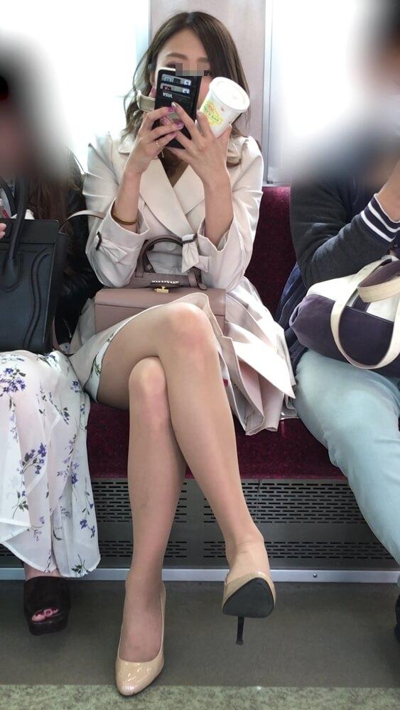 脚を組んでスマホを見ている女性の画像
