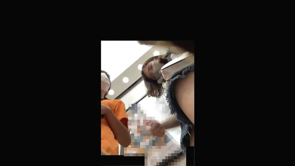 盗撮カメラの方を見て怪しむJCの画像