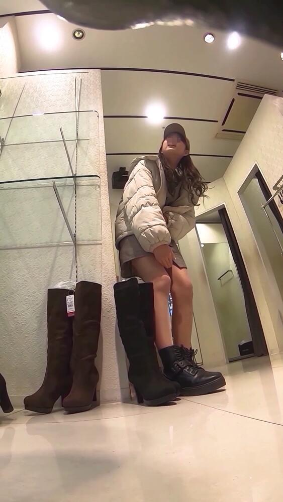 ブーツを履いた感じをジェスチャーで説明する店員さんの姿画像