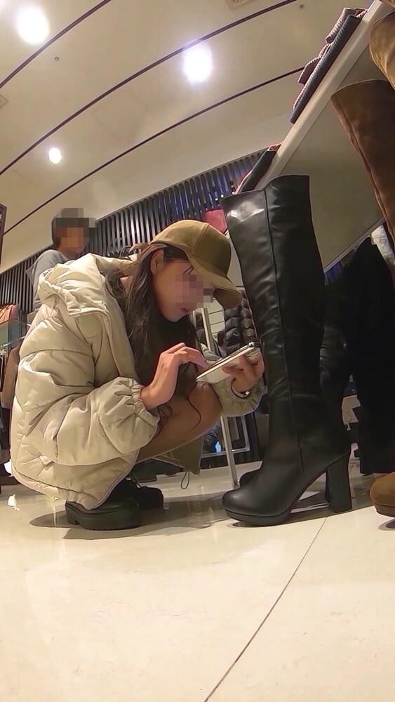 スマホで一生懸命ブーツを履いた画像を検索してくれる店員さんの姿画像