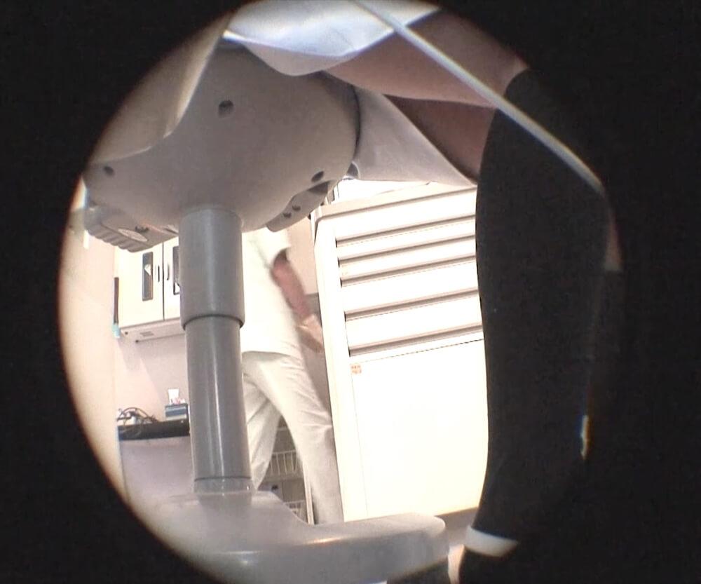医院内の後ろを先生が通っている画像