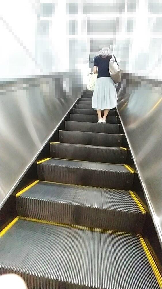 エスカレーターに乗る女性を後ろから映した画像