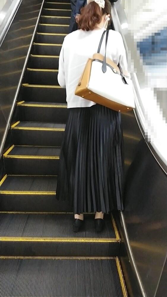 エスカレーターの乗る女性の後ろ姿を映した画像
