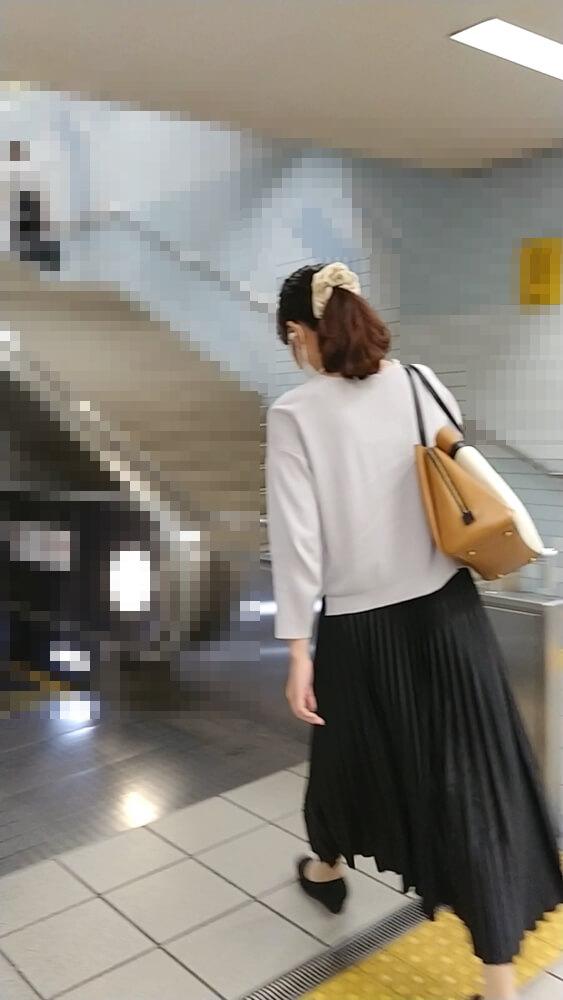 次のエスカレーターへと移動する女性を後ろから映した画像