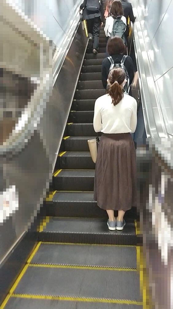 エスカレーターに乗る女性の後ろ姿を映した画像