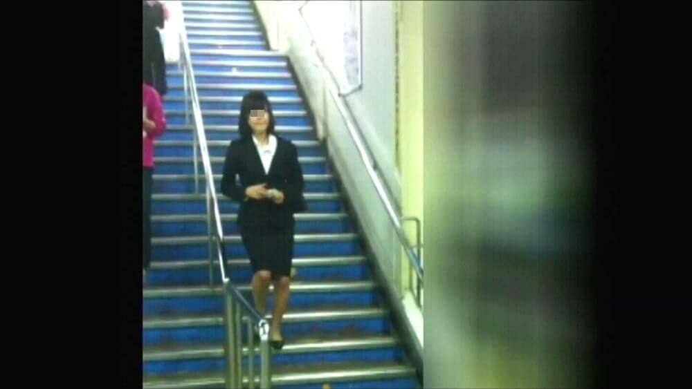 階段を降りてくるリクスー女性の姿を映した画像