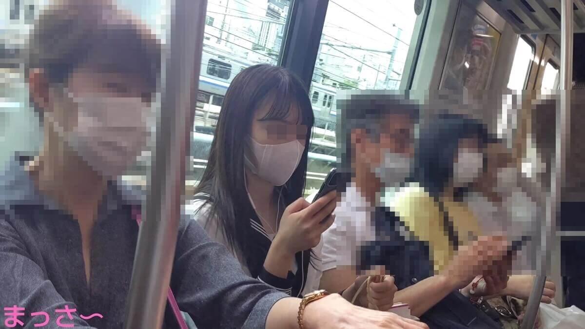 電車内の座席でスマホを見ている美人JK