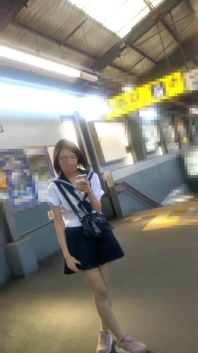 駅のホームでスマホを見る美人JK