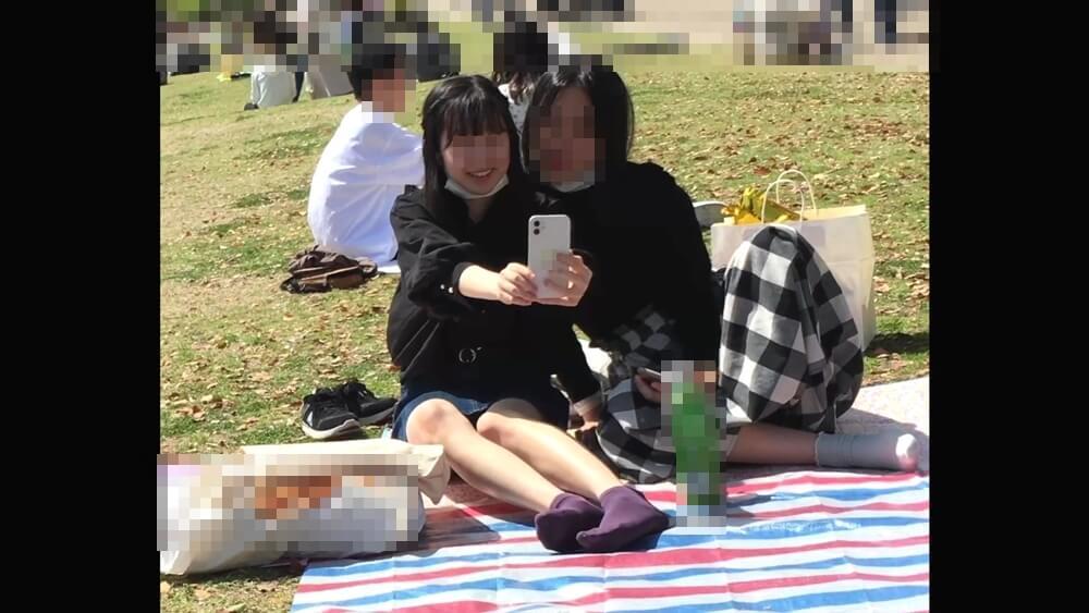 公園で友達と写真を撮る女の子の姿を映した画像