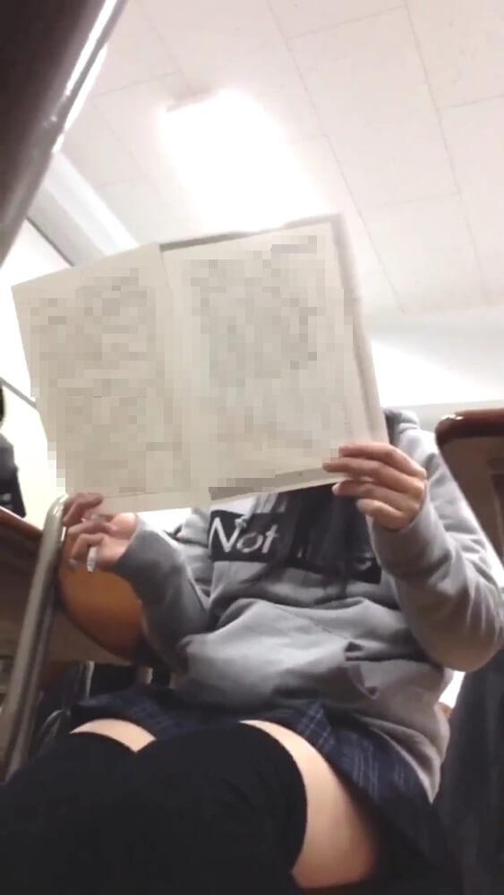 後ろのクラスメイトとプリントを見ているJKを映した画像