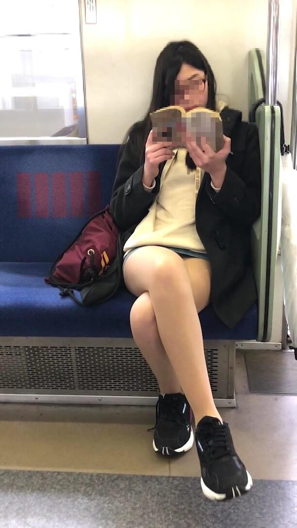 電車の座席に脚を組んで座る女性の姿を映した画像
