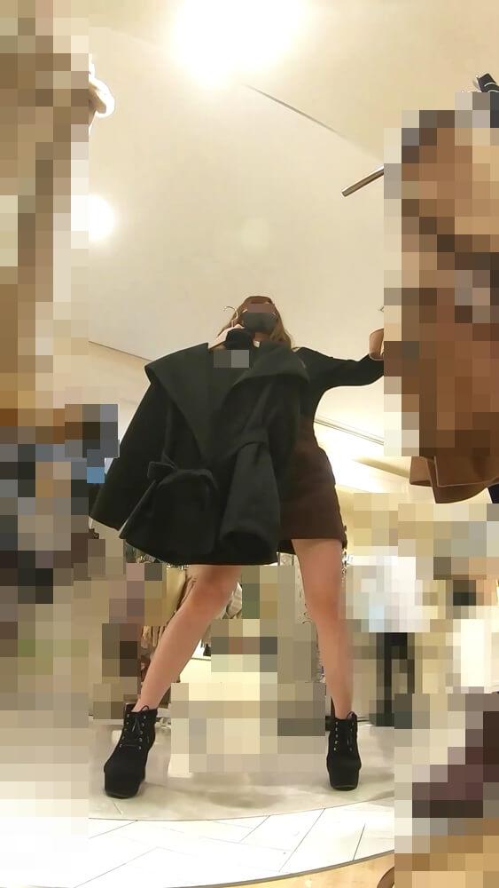 服を体の前で合わせて見せてくれる店員さんを映した画像