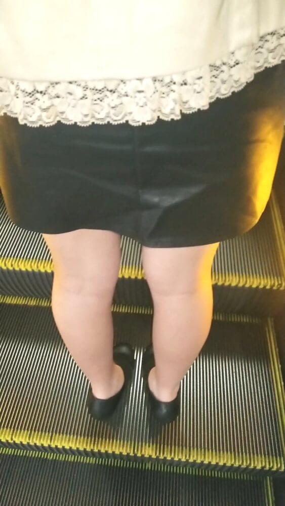 女性の背後から生脚を映した画像